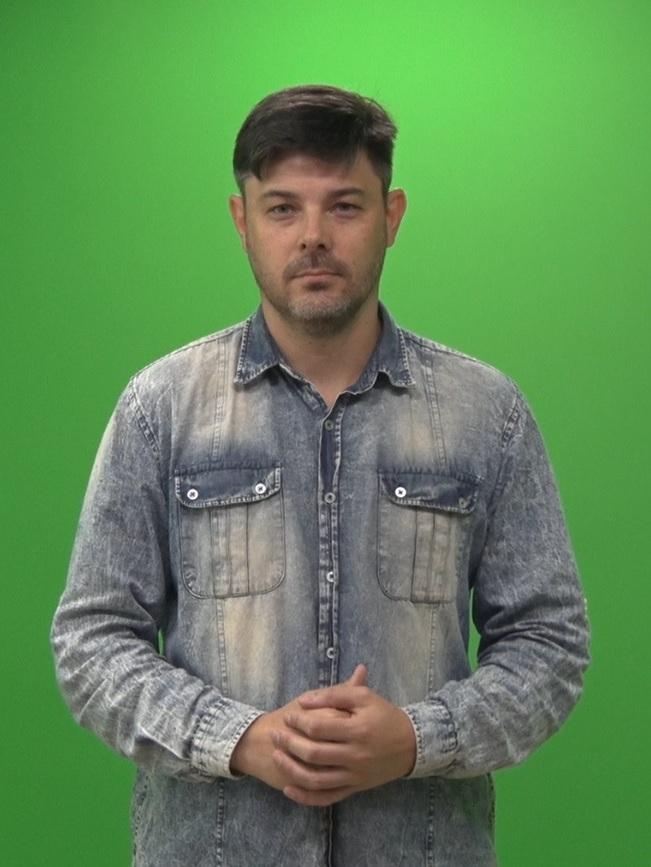 Foto colorida com fundo verde. Nelson é um homem de pele branca, rosto oval, cabelos castanhos claros e curtos, olhos verdes, nariz levemente arrebitado, lábios médios e barba e bigode por fazer. Ele usa camisa jeans de mangas compridas. No vídeo aparece em pé da cintura para cima.
